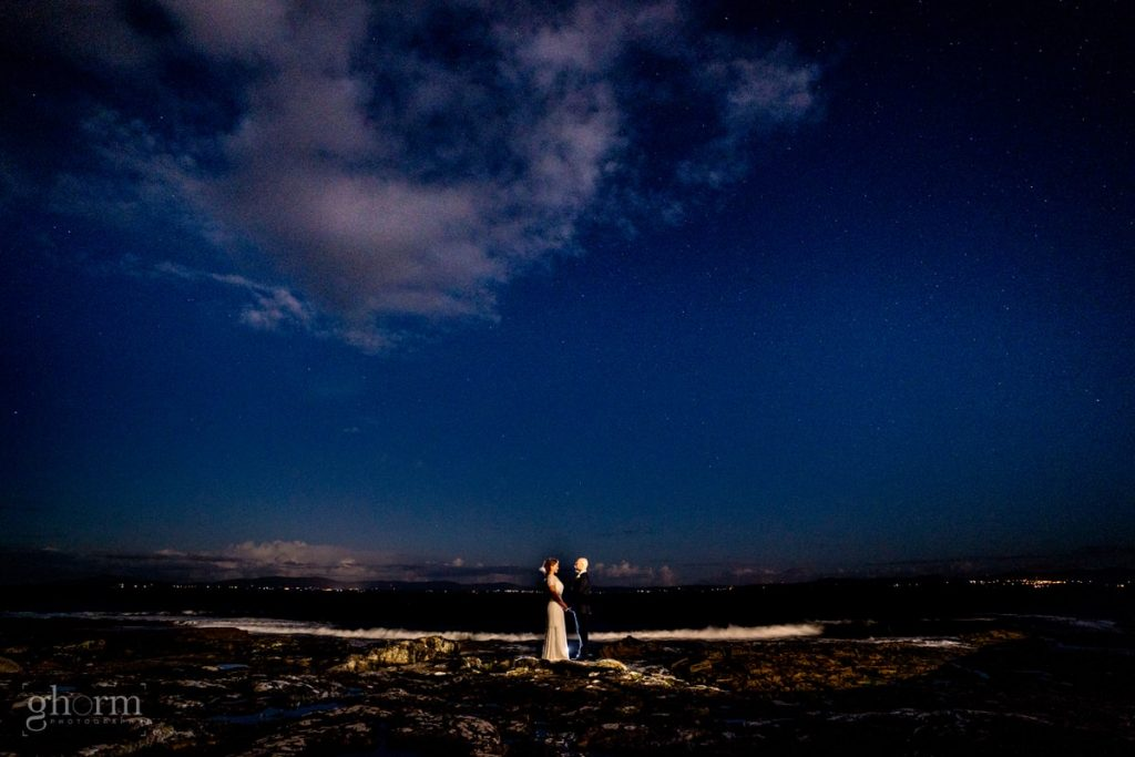 bride and groom on the ocean at night time with the stars and th sleeve lead behind them, Creevet Pier hotel wedding, photos by Paul McGinty from Ghorm Studio Photography.