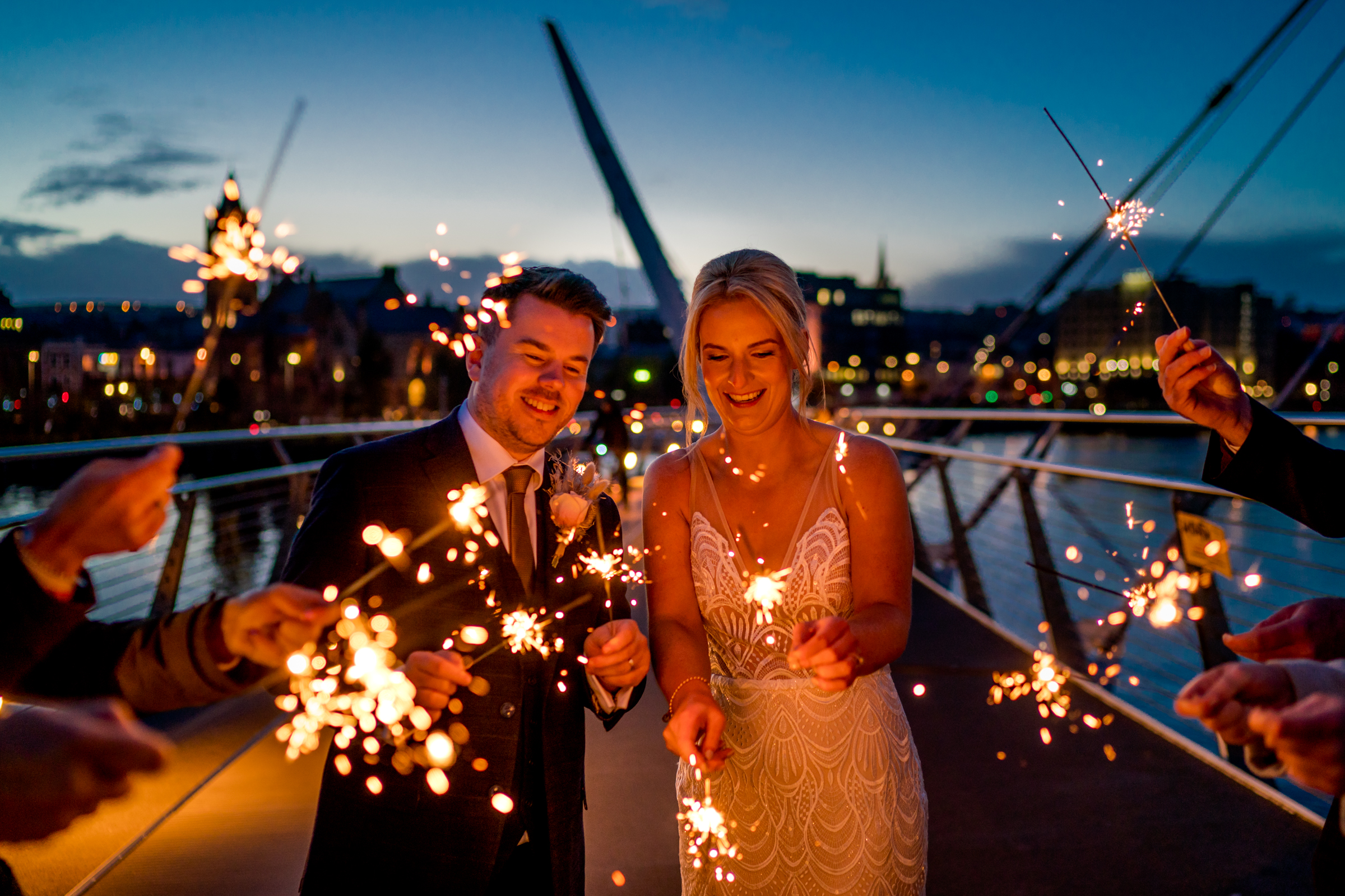 Bride and groom with sparklers on the peace bridge in Derry city as the sun sets. Photo by Paul McGinty from Ghorm Studio Photography, lough Eske, Donegal Town. Covering Sligo, Roscommon, Leitrim and Mayo.