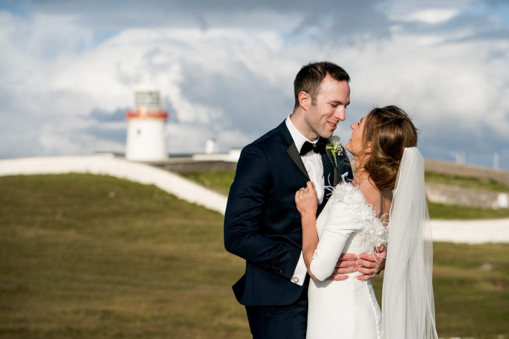 bride and groom in front of lighthouse, Lough Eske castle wedding, Autumn 2019, best wedding venue, photo by Paul McGinty from Ghorm studio photography, Donegal Town, Ireland