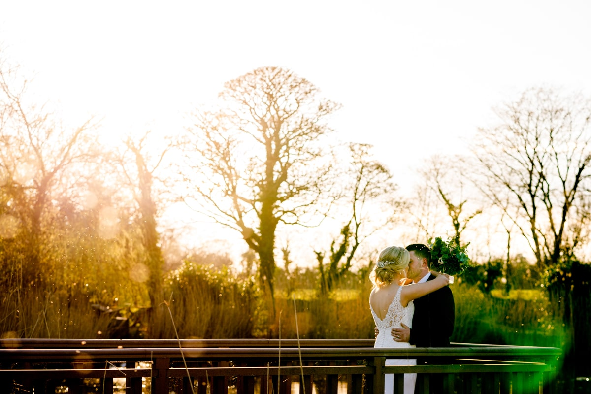 Bride and groom with the sunset behind them.Ballymagarvey wedding photographer, creative, natural, documentary, meath, best wedding photographer ireland, creative wedding photographer ireland, donegal wedding photographer, Paul McGinty Ghorm Studio Photography, Lough Eske, Donegal Town