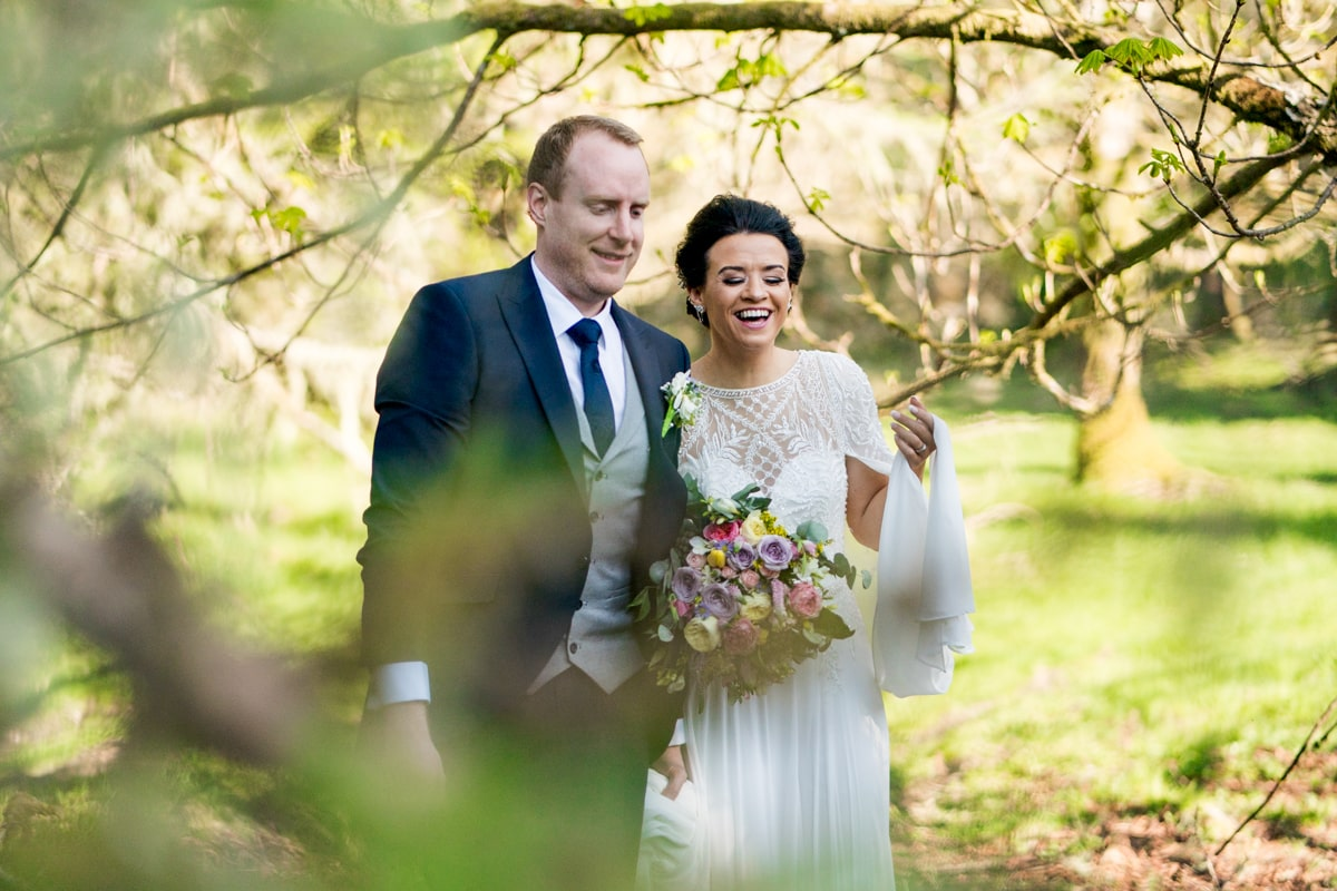 bride and groom walking through a forest, natural wedding photographer. intimate wedding photographer, elopement Ireland, Donegal Sligo, Leitrim Wedding Photographer, Paul McGinty, Ghorm Studio Photography, Lough Eske Donegal Town.