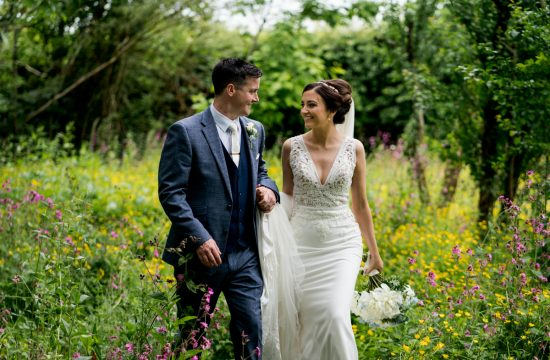 Deborah nd Paddy the bride and groom walking through a meadow field on their wedding day near the Beech Hill House hotel, Co Derry. Photo by Paul Mcginty from Ghorm Studio Photography Lough Eske, Donegal