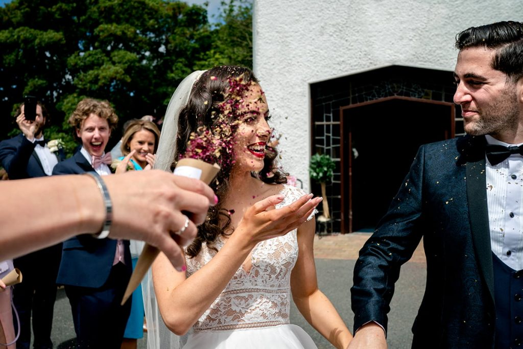 confetti thrown over bride and grooms the leave the church, bride and groom in the Bluestack mountains above Lough Eske, Irish castle wedding, Lough Eske wedding, Paul McGinty, Ghorm Studio Photography