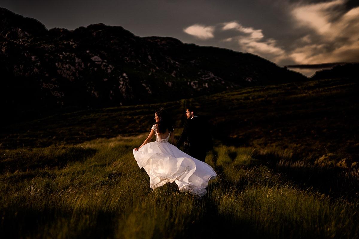bride and groom walking through the bog as the wind blows her wedding dress. Irish castle wedding, Lough Eske wedding, Paul McGinty, Ghorm Studio Photography