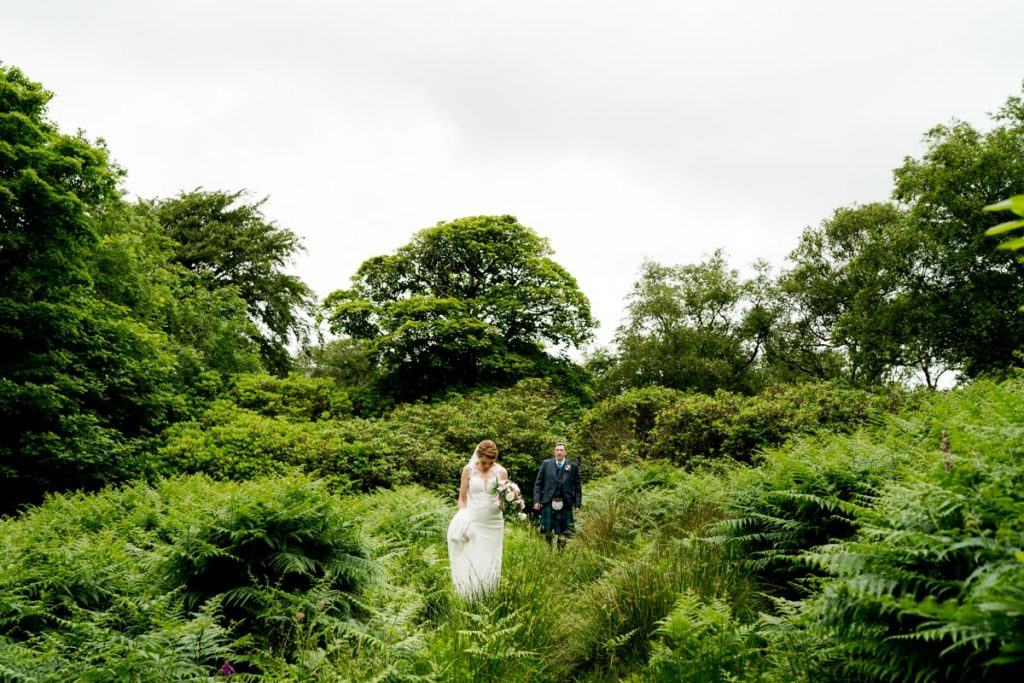 Bride and groom in their hiking boots under Ben Bulben Co Sligo after getting married in WB Yeats church. wedding reception in Lough Eske Castle. Photo by Paul Mcginty, Ghorm Studio Photography