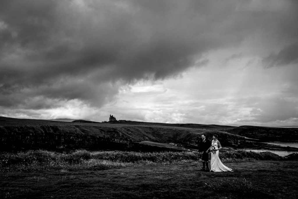 Bride and groom walking across the sea cliffs at Mullaghmore, Co sligo with Cassie Bawn castle . Bride and groom in their hiking boots under Ben Bulben Co Sligo after getting married in WB Yeats church. wedding reception in Lough Eske Castle. Photo by Paul Mcginty, Ghorm Studio Photography