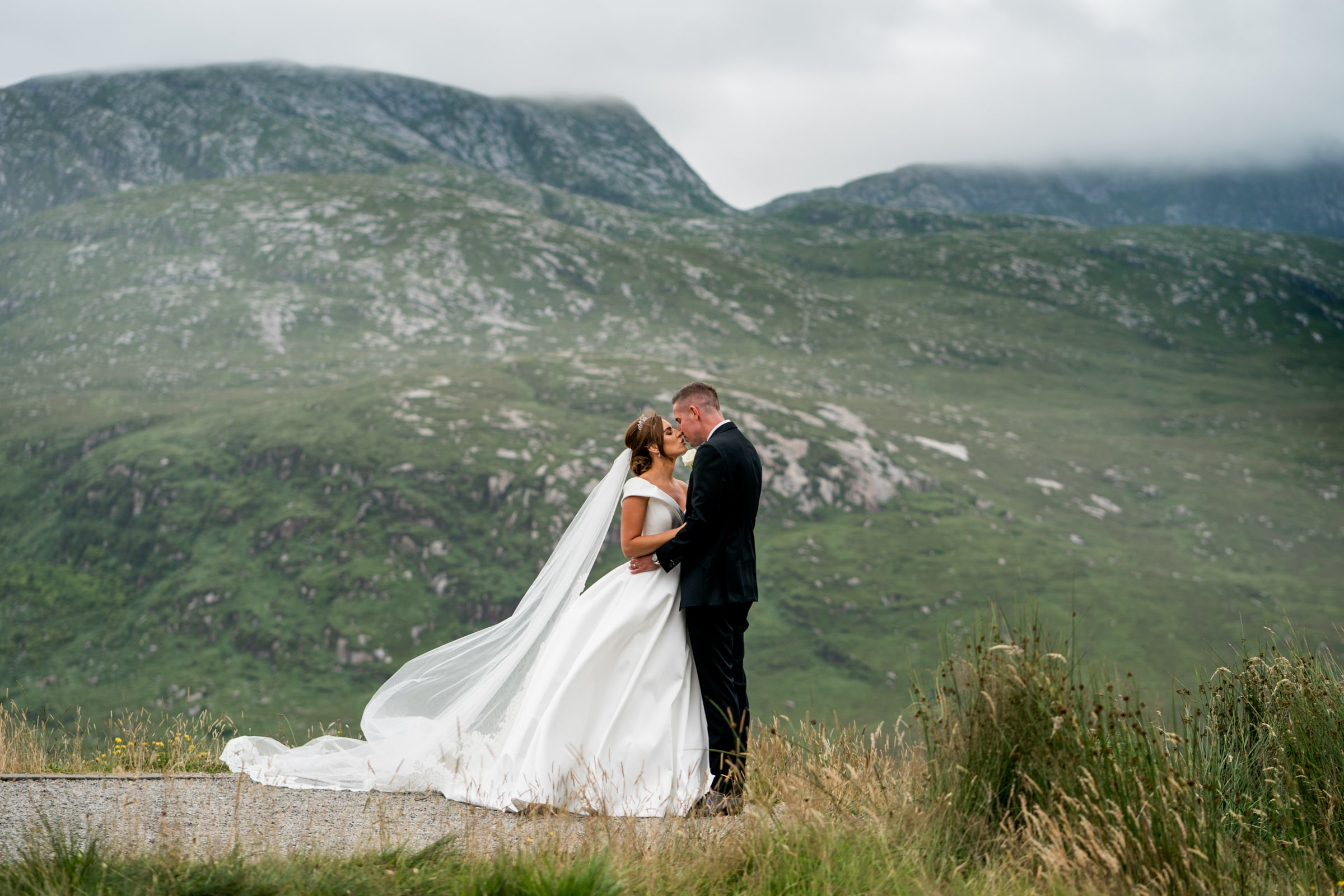 Bride and groom kissing with Dunwely, silver Tassie hotel wedding, donegal wedding venue, photographer donegal, bride and groom in the Poisoned Glen with Mount Errigal in the background, photo by Paul McGinty from Ghorm Studio photography Lough Eske.
