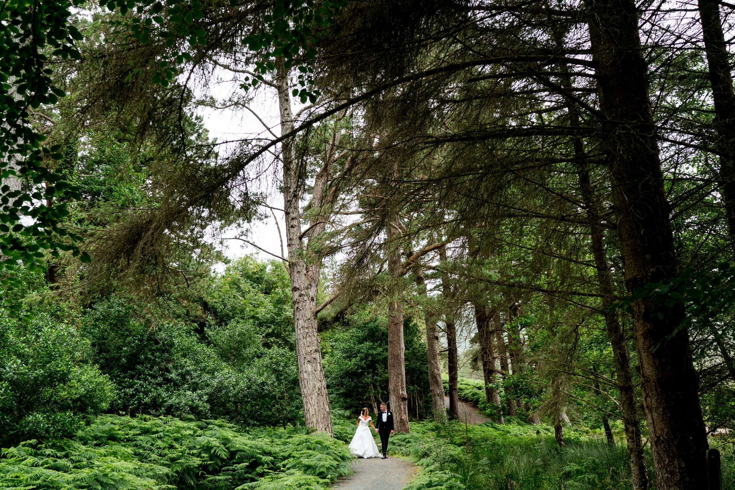 bride and groom walking through a forest in Glenveagh National Park, silver Tassie hotel wedding, donegal wedding venue, photographer donegal, bride and groom in the Poisoned Glen with Mount Errigal in the background, photo by Paul McGinty from Ghorm Studio photography Lough Eske.