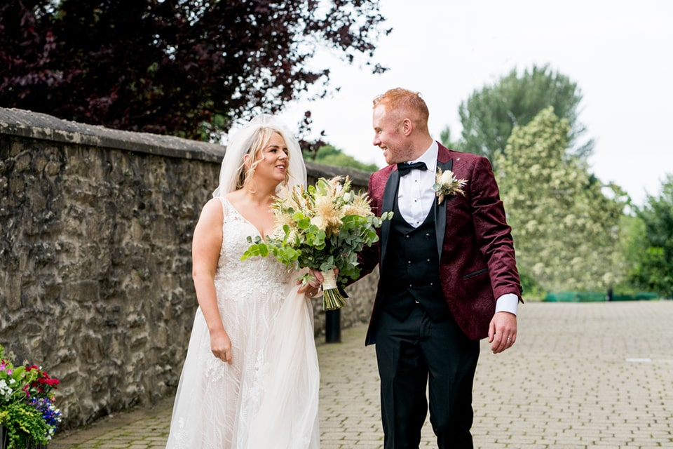 Bride and groom leaving the church, groom holding the bouquet. Silver Tassie hotel, Letterkenny, Co Donegal. Photo by Paul McGinty from Ghorm Studio Photography.