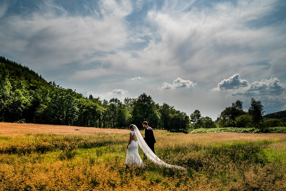 Bride and groom walking hand in hand through a meadow field in Barnesmore Gap, Lough Eske, Mill Park Hotel wedding Donegal Town, Paul McGinty, Ghorm Studio Photography